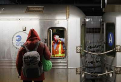 A MTA employee, wears a mask to protect against coronavirus,  waits in the conductors area of a subway car as NYPD and MTA officers wake up sleeping passengers and direct them to the exits at the 207th Street A-train station, Thursday, April 30, 2020, in the Manhattan borough of New York. (AP Photo/John Minchillo)