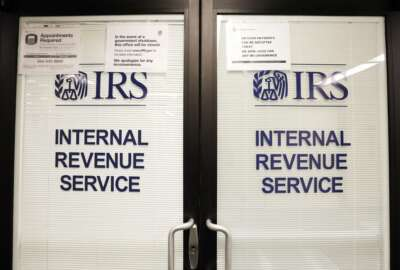 FILE - In this Jan. 16, 2019, file photo, doors at the Internal Revenue Service (IRS) in the Henry M. Jackson Federal Building are locked and covered with blinds as a sign posted advises that the office will be closed during the partial government shutdown in Seattle. Videos and reports claiming that you'll have to pay back the relief checks the federal government is sending to millions of Americans are false, federal agencies confirmed to The Associated Press. (AP Photo/Elaine Thompson, File)