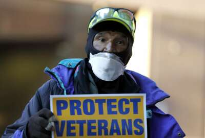 Clarence Shields, an Army veteran, pickets with a small group of activists from the American Federation of Government Employees local 424 and the National Association of Government Employees local R3-19 during the coronavirus pandemic, outside the Baltimore VA Medical Center, Wednesday, April 22, 2020, in Baltimore. The Department of Veterans Affairs is struggling with shortages of workers at its health care facilities as it cares for veterans infected with the novel coronavirus. (AP Photo/Julio Cortez)
