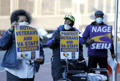 Clarence Shields, center, an Army veteran, pickets with a small group of activists from the American Federation of Government Employees local 424 and the National Association of Government Employees local R3-19 outside the Baltimore VA Medical Center, Wednesday, April 22, 2020, in Baltimore. The Department of Veterans Affairs is struggling with shortages of workers at its health care facilities as it cares for veterans infected with the novel coronavirus. (AP Photo/Julio Cortez)