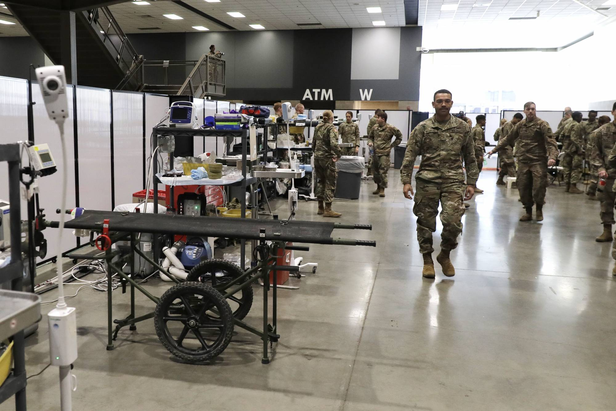 Soldiers walk through a treatment area following a training session at the site of a military field hospital, Sunday, April 5, 2020, at the CenturyLink Field Event Center in Seattle. Officials said the facility, which will be used for people with medical issues that are not related to the coronavirus outbreak, has more than 200 beds and is ready to receive patients. (AP Photo/Ted S. Warren)