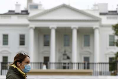 FILE - In this April 1, 2020, file photo a woman wearing a face mask walks past the White House in Washington. The nation's capital, like most of the nation itself, is largely shuttered. (AP Photo/Patrick Semansky, File)