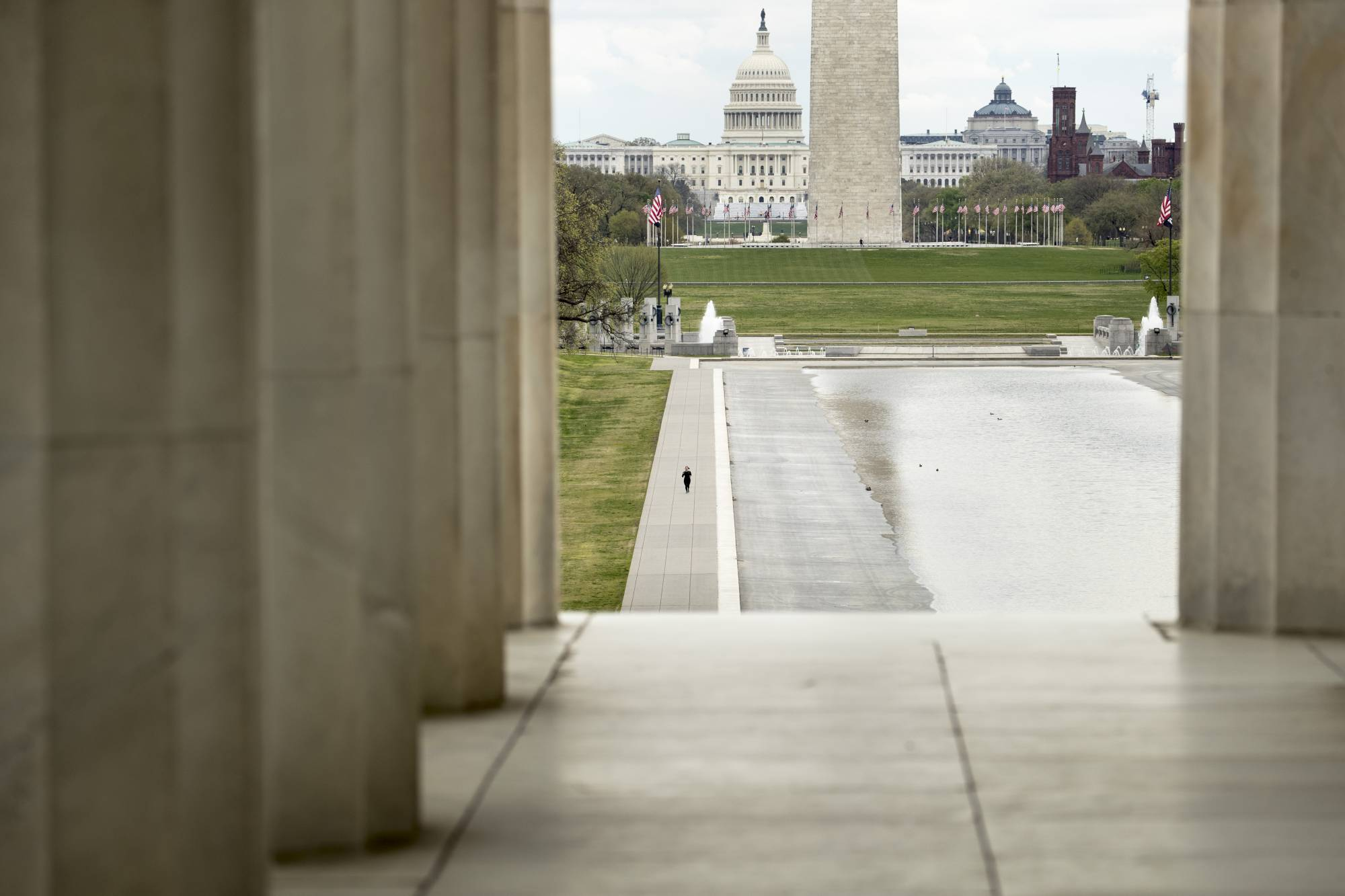 FILE - In this March 31, 2020, file photo the Dome of the U.S. Capitol and the Washington Monument are visible as a lone woman runs along the Reflecting Pool on the National Mall in Washington. The nation's capital, like most of the nation itself, is largely shuttered. (AP Photo/Andrew Harnik, File)