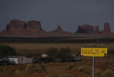 In this April 30, 2020, photo, a sign marks Navajo Drive as Sentinel Mesa, homes and other structures in Oljato-Monument Valley, Utah on the Navajo Reservation, stand in the distance. Even before the pandemic, people living in rural communities and on reservations were among the toughest groups to count in the 2020 census. (AP Photo/Carolyn Kaster)
