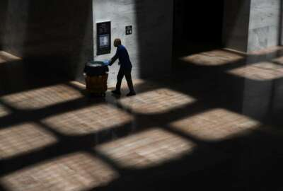 A custodian walks in the Hart Senate Office Building on Capitol Hill in Washington, Tuesday, May 12, 2020. Senate office buildings and the U.S. Capitol remain closed to the public in response to the coronavirus outbreak. (AP Photo/Patrick Semansky)