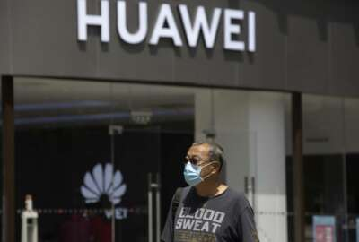 A man wearing a face mask to protect against the coronavirus walks past a Huawei retail store in Beijing on Monday, May 18, 2020. China's commerce ministry says it will take