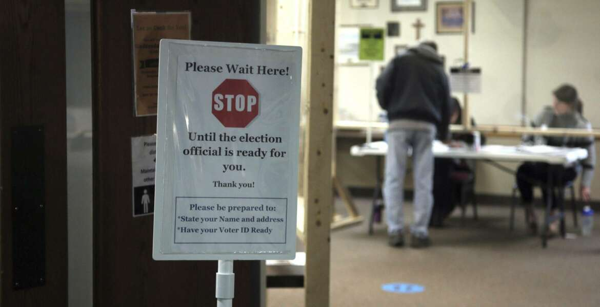 A sign alert voters at the United Methodist Church polling place Tuesday, May 12, 2020, in Hudson, Wis.in Wisconsin's special congressional election to replace retired Republican reality TV star Sean Duffy, in the 7th District race between Republican Tom Tiffany and Democrat Tricia Zunker. (AP Photo/Jim Mone)