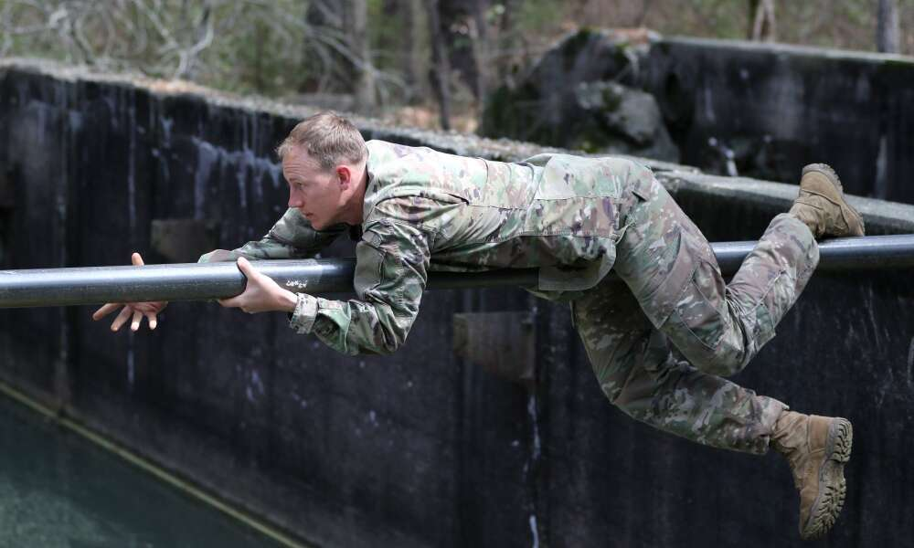 A student assigned to the U.S. Army John F. Kennedy Special Warfare Center and School maneuvers across an obstacle during the evasion phase of Survival Evasion Resistance and Escape Level-C training (SERE) at Camp Mackall, North Carolina, March 21, 2020. Soldiers in SERE underwent intensive training in support of the Code of the Conduct, and were taught survival fieldcraft skills, techniques of evasion, resistance to exploitation and resolution skills along with critical life saving techniques for austere conditions that are key to survival and the ability to return with honor.