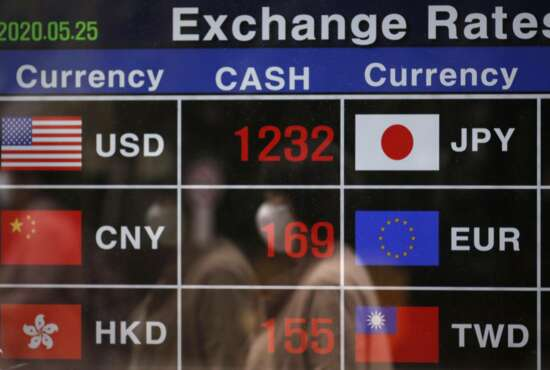 A woman wearing a face mask is reflected on an electronic foreign currency exchange rates in downtown Seoul, South Korea, Monday, May 25, 2020. Asian shares are mostly higher, with Tokyo stocks gaining on expectations that a pandemic state of emergency will be lifted for all of Japan. But shares fell in Hong Kong on Monday after police used tear gas to quell weekend protests over a proposed national security bill for the former British colony. (AP Photo/Lee Jin-man)