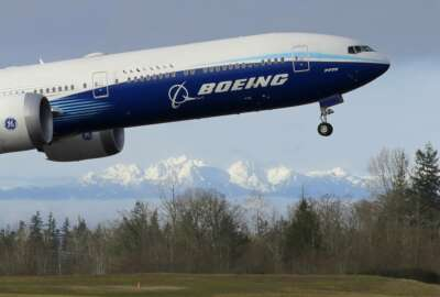 FILE - In this Jan. 25, 2020, file photo a Boeing 777X airplane takes off on its first flight with the Olympic Mountains in the background at Paine Field in Everett, Wash.  Boeing on Wednesday, May 27, is cutting more than 12,000 jobs through layoffs and buyouts as the coronavirus pandemic seizes the travel industry. And the aircraft maker says more cuts are coming.  (AP Photo/Ted S. Warren, File).