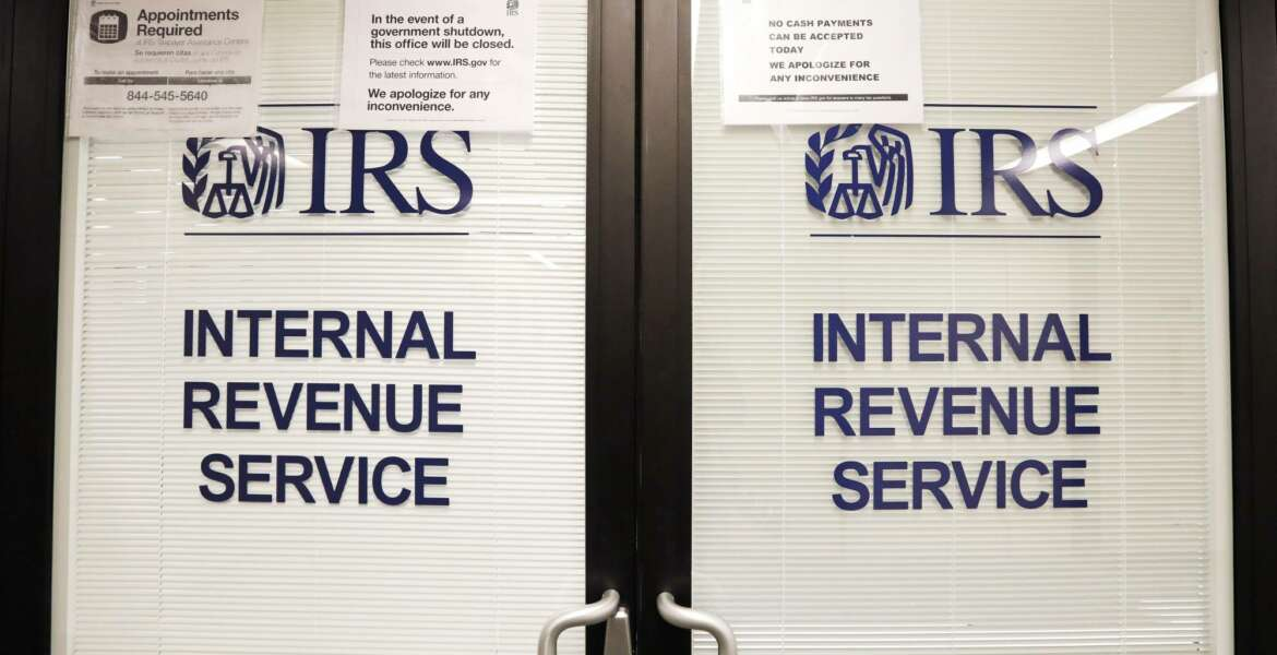 FILE - In this Jan. 16, 2019, file photo, doors at the Internal Revenue Service (IRS) in the Henry M. Jackson Federal Building are locked and covered with blinds as a sign posted advises that the office will be closed during the partial government shutdown in Seattle. (AP Photo/Elaine Thompson, File)