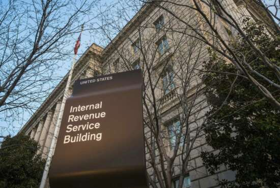 """FILE - This April 13, 2014, file photo shows the Internal Revenue Service (IRS) headquarters building in Washington. The Treasury Department and the IRS are urging taxpayers who want to get their economic impact payments directly deposited to their bank accounts to enter their information online by Wednesday, May 11, 2020. The IRS said that people should use the """"Get My Payment"""" tool on the IRS website by noon on Wednesday to provide their direct deposit information. (AP Photo/J. David Ake, File)"""