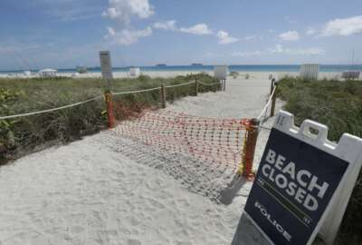 FILE - In this Tuesday, March 31, 2020 file photo, an entrance to a beach is shown closed, in Miami Beach, Florida's famed South Beach. Memorial Day weekend historically signifies the start of the summer vacation season as families throughout the U.S. plan trips to Florida's beaches and theme parks. Miami-Dade County officials aren't expecting crowds, as the beaches remain closed. (AP Photo/Wilfredo Lee, File)