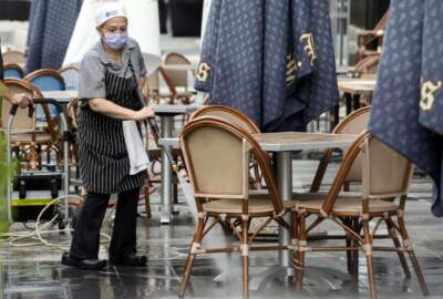 In this May 27, 2020, photo, a worker at Brasserie Beck, a restaurant along K Street in downtown Washington, power washes the outdoor seating area. The nation's capital is starting to reopen, Starting May 29, a tiny slice of pre-pandemic normality starts returning to the city as the three-month old coronavirus stay-home order is replaced by the first phase of a reopening plan(AP Photo/Jon Elswick)