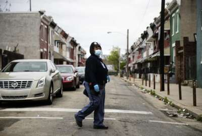 United States Postal Service carrier Henrietta Dixon walks her route to deliver mail in Philadelphia, Wednesday, May 6, 2020. From coastal Maine to Philadelphia's close-knit neighborhoods, many residents call the service essential to their communities. (AP Photo/Matt Rourke)