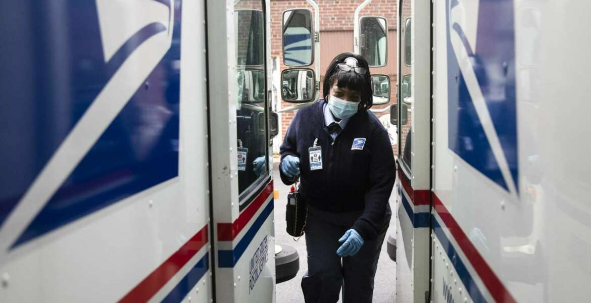 In this Wednesday, May 6, 2020, photo, United States Postal Service carrier Henrietta Dixon gets into her truck to deliver mail in Philadelphia. (AP Photo/Matt Rourke)