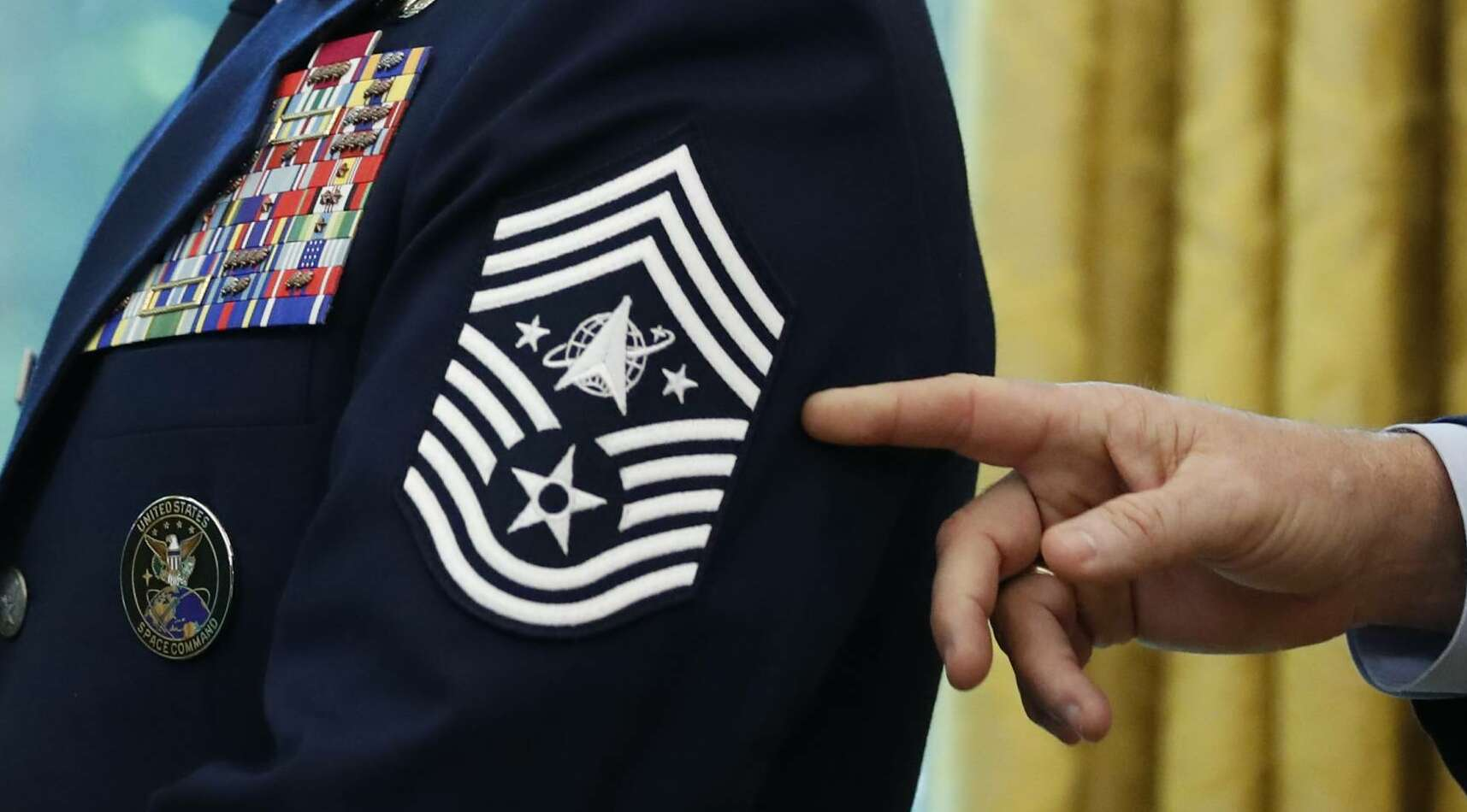 Chief Master Sgt. Roger Towberman displays his insignia during a presentation of the United States Space Force flag in the Oval Office of the White House, Friday, May 15, 2020, in Washington. (AP Photo/Alex Brandon)