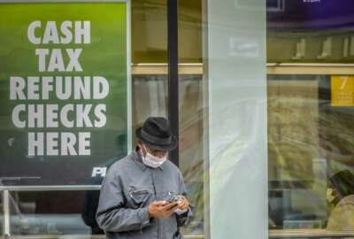 In this April 3, 2020, photo, a man wearing a face mask due to COVID-19 concerns stands outside a check cashing service center in the Brooklyn borough of New York. While millions of U.S. workers have already received a quick relief payment from the federal treasury through direct deposit, millions of others without traditional bank accounts must wait weeks for paper checks. Advocates for the poor say this is an opportunity to get many of those who are unbanked into the formal financial system. (AP Photo/Bebeto Matthews)