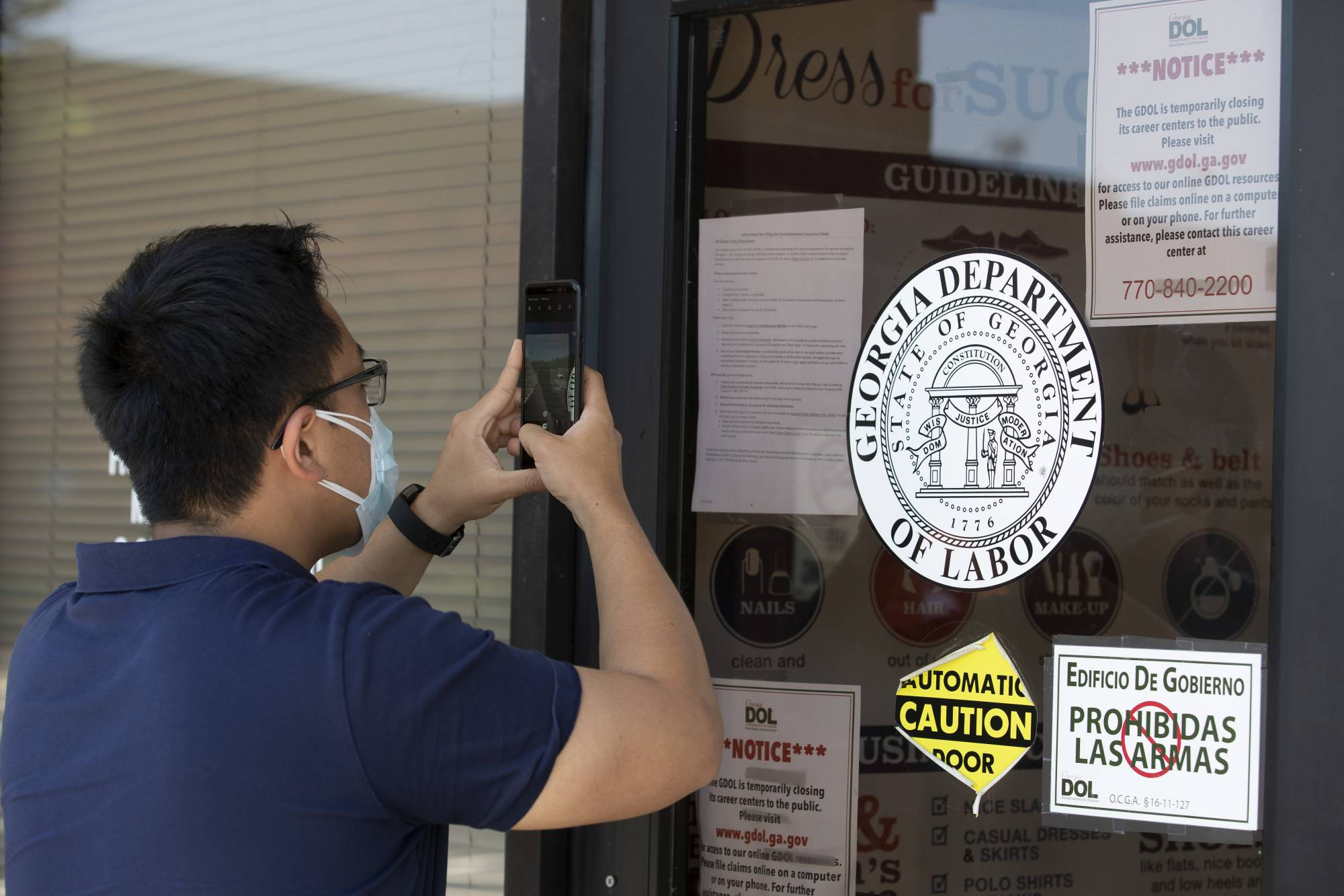 A man uses his phone to copy phone numbers posted on the locked doors of a Georgia Department of Labor office Thursday, May 7, 2020, in Norcross Ga. (AP Photo/John Bazemore)