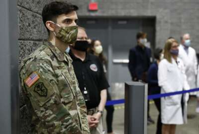 A member of the U.S. Army and medical professionals practice social distancing as they attend a news conference with District of Columbia Mayor Muriel Bowser at a temporary alternate care site constructed in response to the coronavirus outbreak inside the Walter E. Washington Convention Center in Washington, Monday, May 11, 2020. (AP Photo/Patrick Semansky)