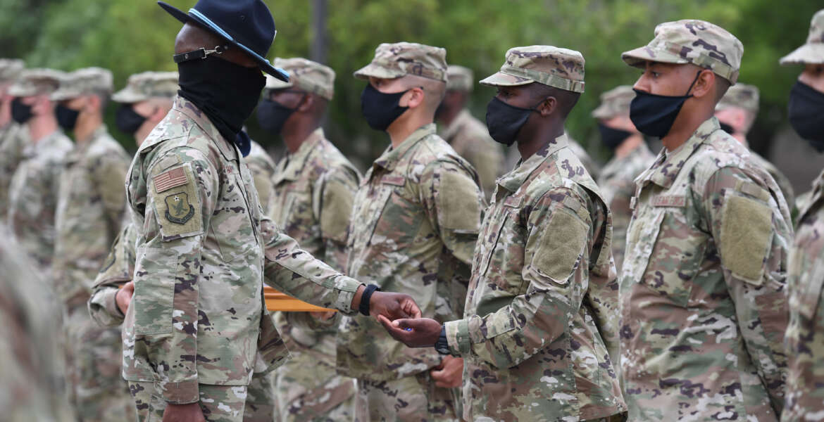 U.S. Air Force Tech. Sgt. Rashawn Duffy, 37th Training Wing Detachment 5 military training instructor, presents a coin to an Airman during the basic military training coining ceremony outside of Erwin Manor at Keesler Air Force Base, Mississippi, May 14, 2020. Nearly 60 Airmen from the 37th TRW Detachment 5 completed the six-week basic military training course. Due to safety concerns stemming from COVID-19, the Air Force sent new recruits to Keesler to demonstrate a proof of concept to generate the force at multiple locations during contingencies. The flight was the first to graduate BMT at Keesler since 1968. (U.S. Air Force photo by Kemberly Groue)