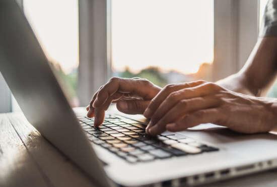Men is typing on laptop computer keyboard