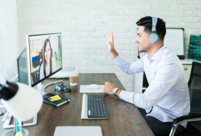 Confident young salesman waving at colleague during video call on computer at desk