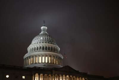 FILE - In this Dec. 9, 2019, file photo mist rolls over the U.S. Capitol dome on Capitol Hill in Washington.  The federal government recorded a budget deficit of $1.88 trillion for the first eight months of 2020, larger than even any annual shortfalls in U.S. history. The sea of red ink grew as government spending shot up to deal with the coronavirus pandemic and tax revenue shrank when millions lost their jobs. (AP Photo/Patrick Semansky, File)