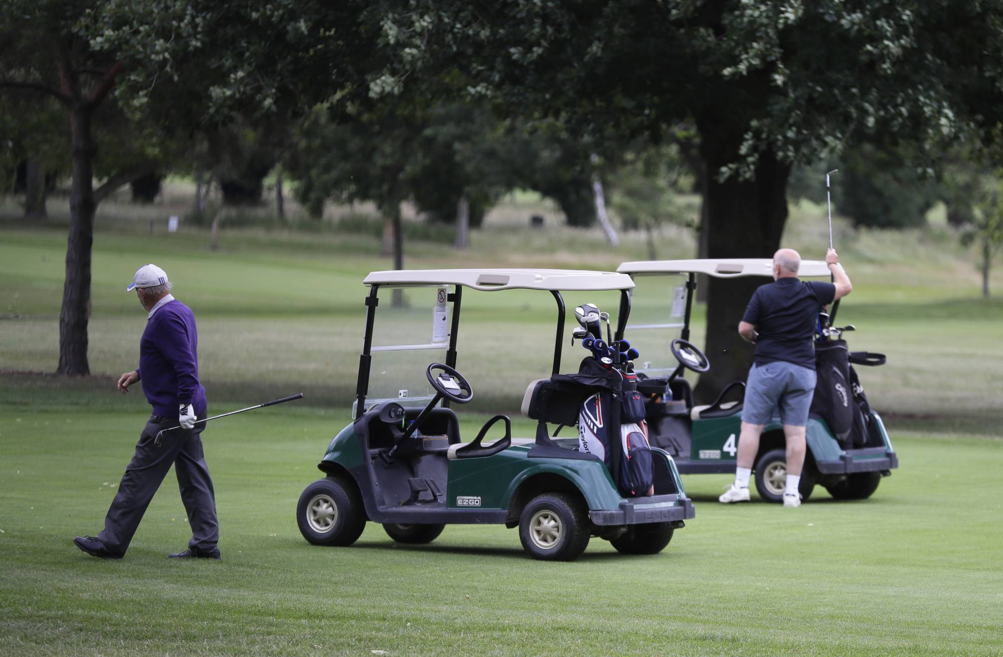 Golfers play on the golf course which would usually be used as a car park for Wimbledon tennis tournament visitors, in Wimbledon in London, Monday, June 29, 2020. The 2020 Wimbledon Tennis Championships, due to start Monday were cancelled due to the Coronavirus pandemic. (AP Photo/Kirsty Wigglesworth)