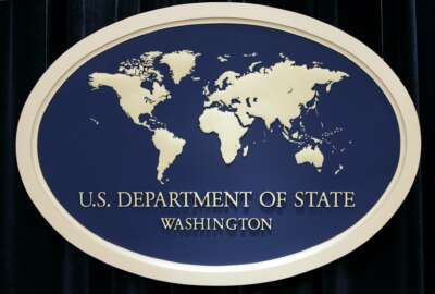 FILE  - This Aug. 10, 2006, file photo shows the sign used as the backdrop for press briefings at the U.S. Department of State in Washington. More of the first volunteers are starting to trickle back to their desks at federal agencies in the coronavirus lockdown. In the third month after Americans began sheltering in place and worksites began closing, the Energy Department says the first voluntary returns of a small number of headquarters workers began Monday. The State Department and Agriculture Department also have some workers returning to job places this month. (AP Photo/Charles Dharapak. File)