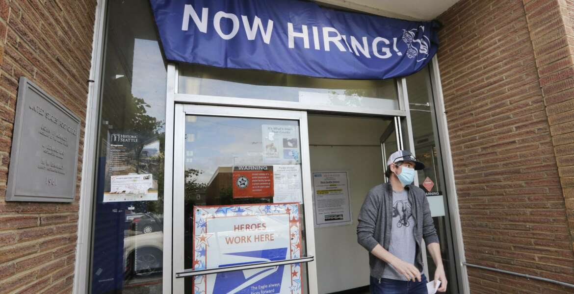 FILE - In this June 4, 2020, file photo, a customer walks out of a U.S. Post Office branch and under a banner advertising a job opening, in Seattle. The U.S. government will issue its latest snapshot Thursday, June 18, of the layoffs that have left millions unemployed but have slowed as businesses have increasingly reopened and rehired some of their laid-off workers. (AP Photo/Elaine Thompson, File)