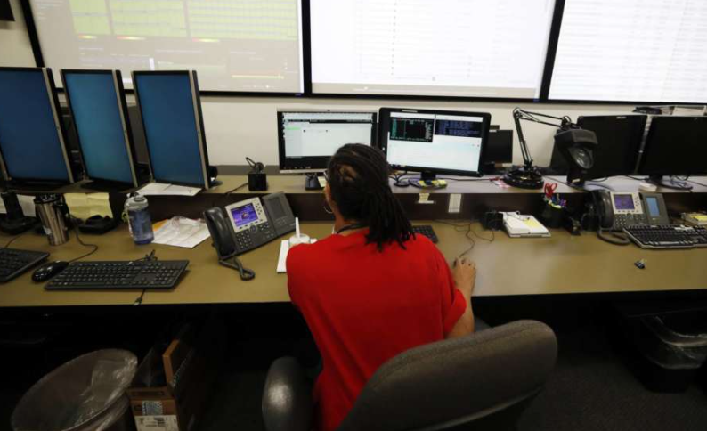 """In this Thursday, Sept. 12, 2019, photograph, monitors check their screens in the Governor's Office of Information Technology in downtown Denver. Some cybersecurity professionals are concerned that insurance policies designed to limit the damage of ransomware attacks might actually be encouraging hackers. """"We don't know what that ransom payment is going to fund,"""" said Brandi Simmons, a spokeswoman for the office. """"As a state government, we don't want to be in a position of funding cyberterrorists."""" (AP Photo/David Zalubowski)"""