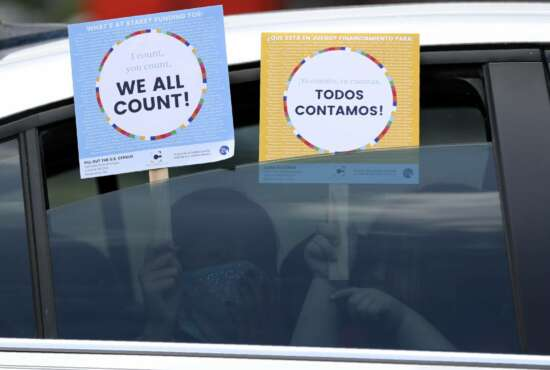 FILE - In this June 25, 2020, file photo, two young children hold signs through the car window that make reference to the 2020 U.S. Census as they wait in the car with their family at an outreach event in Dallas. Thousands of census takers are about to begin the most labor-intensive part of America's once-a-decade headcount (AP Photo/Tony Gutierrez, File)