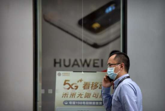 A man wearing a face mask to protect against the new coronavirus talks on his smartphone as he walks past a Huawei store in Beijing, Wednesday, July 1, 2020. China on Wednesday demanded Washington stop