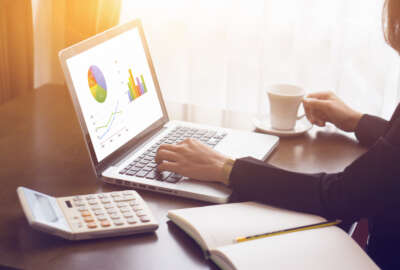 accounting,financial,woman typing on a laptop with chart graph on screen,for analyzing financial chart,writing business plan,open net-book,phone,tablets,Accountants work reports,coffee cup
