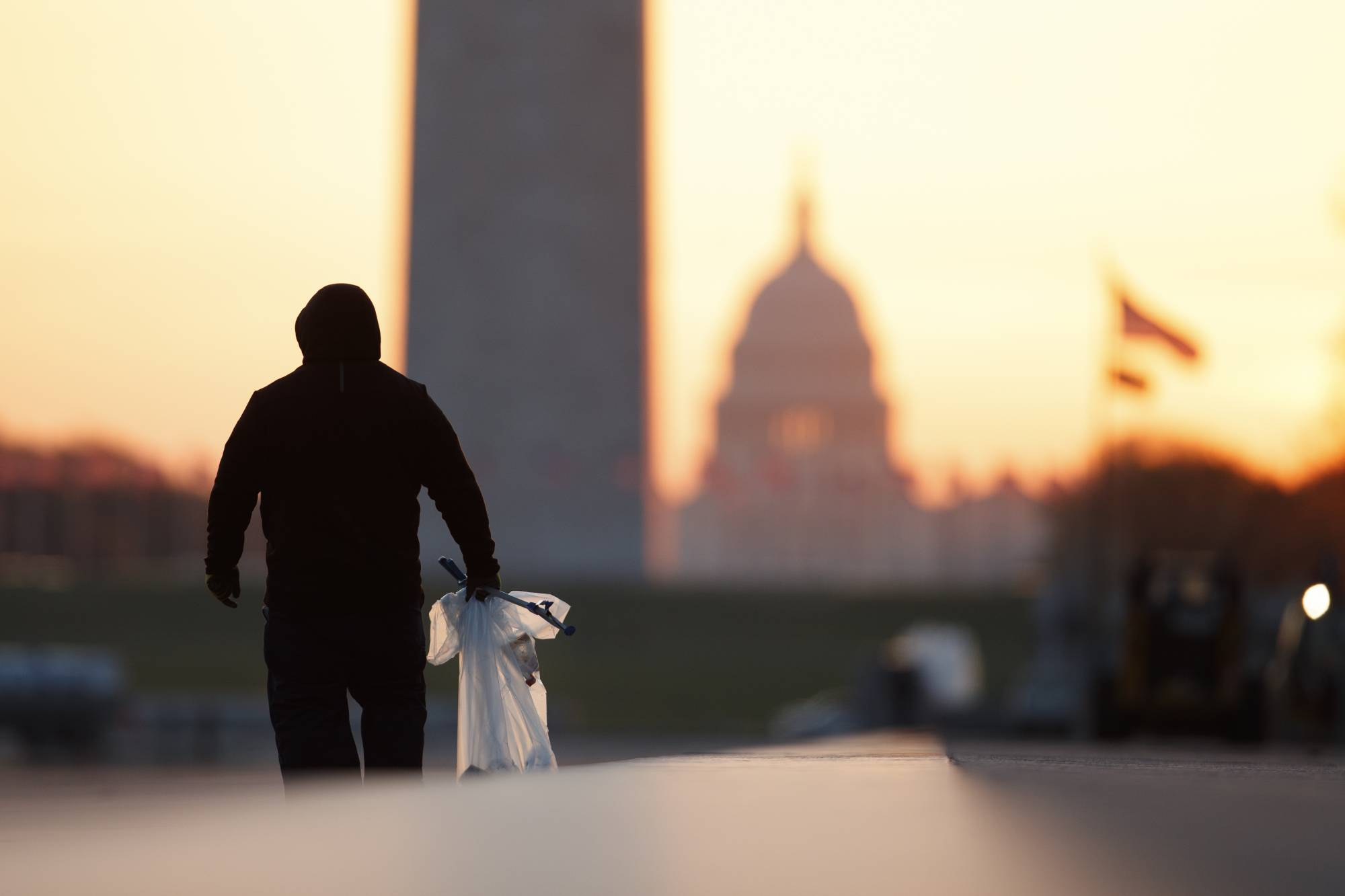 FILE - In this March 18, 2020, file photo a National Park Service worker picks up trash along the drained Lincoln Memorial Reflecting Pool as the Washington Monument and the U.S. Capitol are seen in the distance in Washington, at sunrise. Nearly 3,000 federal workers have filed compensation claims for having contracted COVID-19 on the job, a number that is expected to double by early next month, according to a Department of Labor review. (AP Photo/Carolyn Kaster, File)