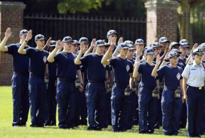 FILE — In this July 1, 2019 file photo, members of the U.S. Coast Guard Academy Class of 2023 take their oath of office on the first day of Swab Summer in New London, Conn. The school, like other service academies and military training centers, has made major changes because of the coronavirus pandemic. That means the eight weeks of boot camp for new cadets, known as