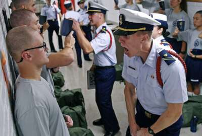 FILE - In this July 1, 2019, file photo, Whisky 2 company Cadre Jacob Denns, right, shouts instructions to swab Nicolas Fisher, left, of Pelham, N.H., on the first day of a seven-week indoctrination to military academy life for the Class of 2023 at the U.S. Coast Guard Academy in New London, Conn. The school, like other service academies and military training centers, has made major changes because of the coronavirus pandemic. That means the eight weeks of boot camp for new cadets, known as