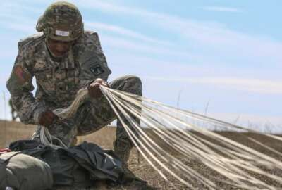 """Spc. Adrian Marchman, a human resource specialist assigned to the XVIII Airborne Corps conducts """"parachute recovery"""" after jumping from 1,200 feet during an Airborne assault at Sicily Drop Zone on Fort Bragg, N.C., Feb. 23, 2017."""