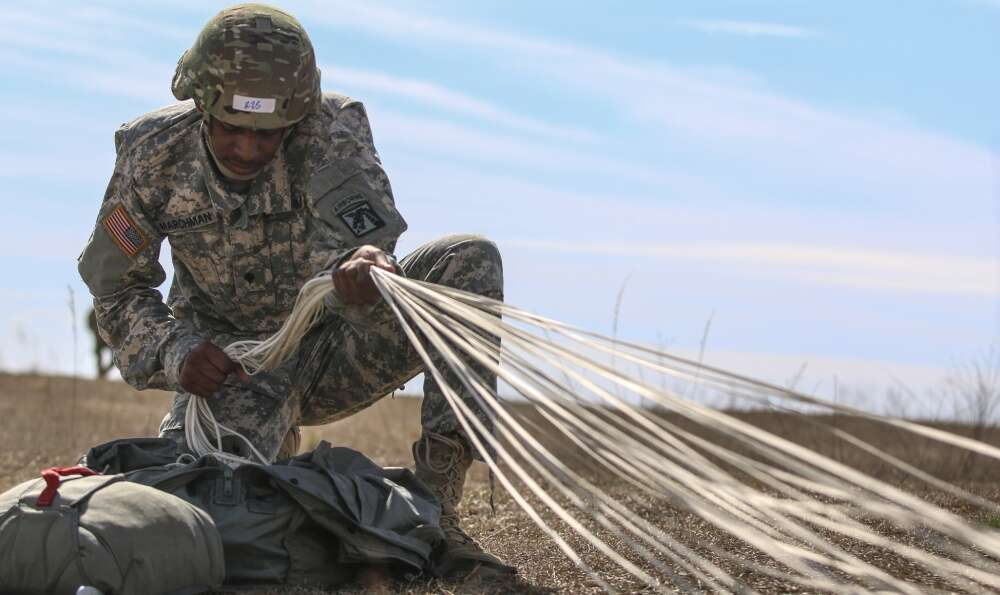 "Spc. Adrian Marchman, a human resource specialist assigned to the XVIII Airborne Corps conducts ""parachute recovery"" after jumping from 1,200 feet during an Airborne assault at Sicily Drop Zone on Fort Bragg, N.C., Feb. 23, 2017."