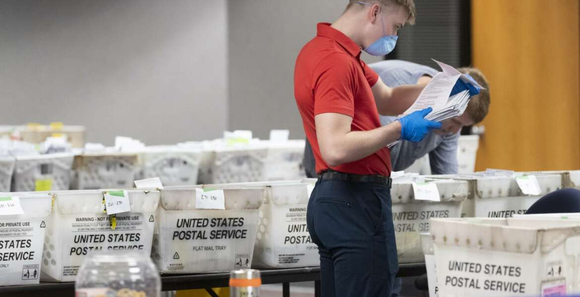 FILE - In this April 8, 2020 file photo, a City of Milwaukee Election Commission worker processes and sorts absentee ballots for Wisconsin's primary election, in downtown Milwaukee, Wis. U.S. Postal Service warnings that it can't guarantee ballots sent by mail will arrive on time have put a spotlight on the narrow timeframes most states allow to request and return those ballots. (Mark Hoffman/Milwaukee Journal-Sentinel via AP, File)