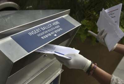 FILE - In this July 7, 2020, file photo a woman wearing gloves drops off a mail-in ballot at a drop box in Hackensack, N.J. With the Trump administration openly trying to undermine mail-in voting this fall, some election officials around the country are hoping to bypass the Postal Service by installing lots of ballot drop boxes in libraries, community centers and other public places. (AP Photo/Seth Wenig, File)