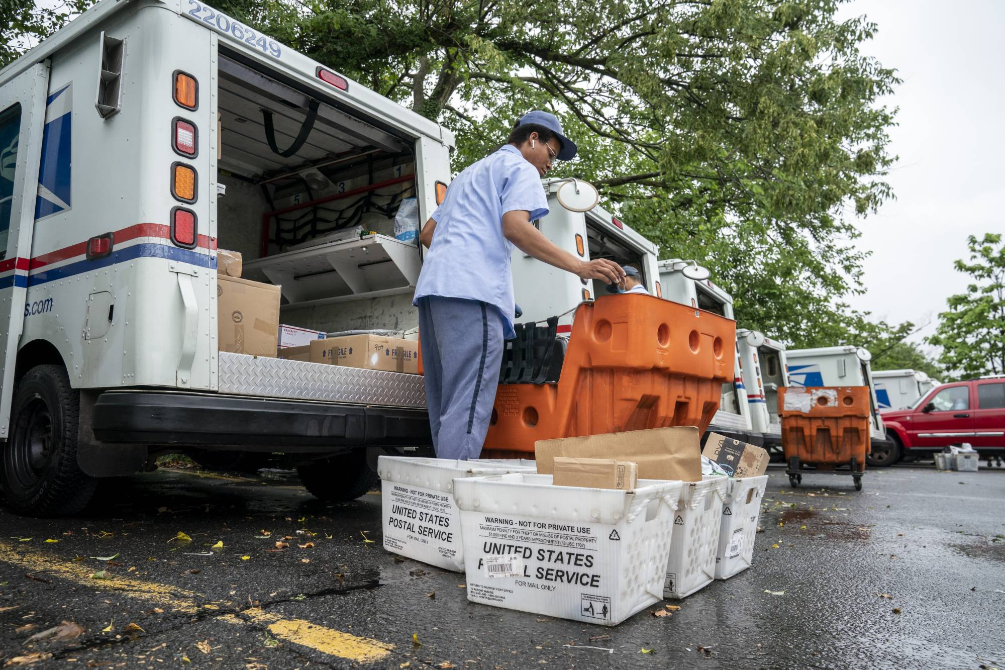 Letter carriers load mail trucks for deliveries at a U.S. Postal Service facility in McLean, Va., Friday, July 31, 2020. Delays caused by an increase in voting by mail may contribute to public doubts about the results. The public might not know the winner of the presidential race on Election Day because of a massive shift to voting by mail during the coronavirus pandemic. That's because mail ballots take longer to count because of security procedures and laws in some states that limit when they can be processed.  (AP Photo/J. Scott Applewhite)