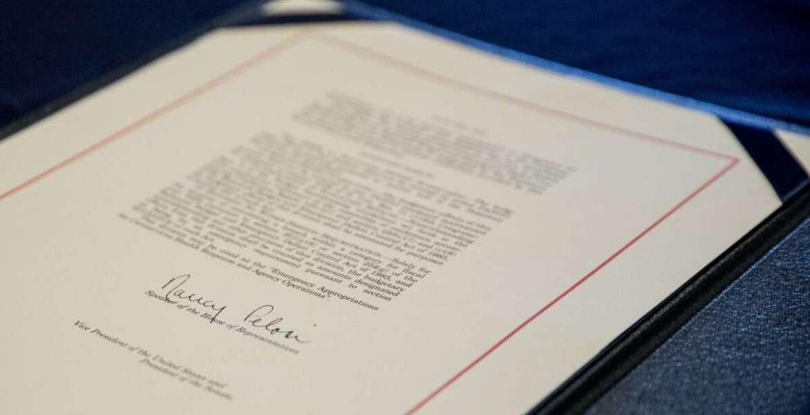FILE - This March 27, 2020 file photo shows the signature of House Speaker Nancy Pelosi, D-Calif., on the Coronavirus Aid, Relief, and Economic Security (CARES) Act after it passed in the House on Capitol Hill in Washington. Since the pandemic began, Congress has set aside trillions of dollars to ease the crisis. A joint KHN and Associated Press investigation finds that many communities with big outbreaks have spent little of that federal money on local public health departments for work such as testing and contact tracing. (AP Photo/Andrew Harnik, File)