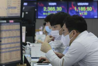 Currency traders watch monitors at the foreign exchange dealing room of the KEB Hana Bank headquarters in Seoul, South Korea, Thursday, Aug. 27, 2020. Asian stock markets retreated Thursday as investors looked ahead to a speech by the U.S. Federal Reserve chairman for signs of more support to an economic recovery. (AP Photo/Ahn Young-joon)