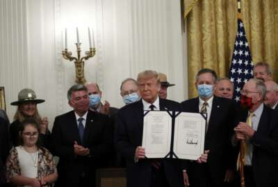 President Donald Trump poses for a photo during a signing ceremony for H.R. 1957 –