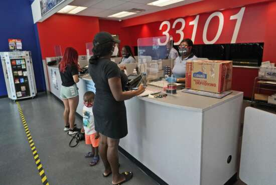 Postal workers attend customers at the Flagler Station post office, Tuesday, Aug. 25, 2020, in Miami. The pandemic has pushed the Postal Service into a central role in the 2020 elections, with tens of millions of people expected to vote by mail rather than in-person. At the same time, Trump has acknowledged he is withholding emergency aid from the service to make it harder to process mail-in ballots, as his election campaign legally challenges mail voting procedures in key states. (AP Photo/Wilfredo Lee)