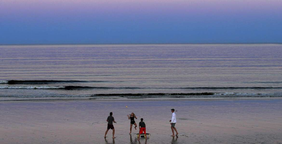 A group of people play Spikeball at twilight on the beach, Thursday, Aug. 7, 2020, in Ocean Park, Maine. As the summer tourist season reaches its peak Maine's coronavirus positivity rate remains among the lowest in the nation. (AP Photo/Robert F. Bukaty)