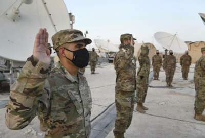In this photo released by the U.S. Air Force, Airmen deployed to Al-Udeid Air Base, Qatar, raise their right hands during an enlistment ceremony as they transferred into the Space Force at Al-Udeid Air Base, Qatar, Tuesday, Sept. 1, 2020. Space Force now has a squadron of 20 members stationed at the Qatari base in its first foreign deployment. The force represents the sixth branch of the U.S. military and the first new military service since the creation of the Air Force in 1947. (Staff Sgt. Kayla White/U.S. Air Force via AP)