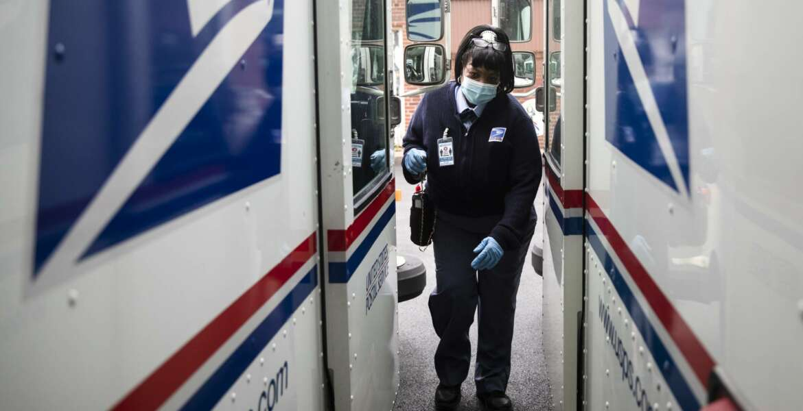 FILE - In this May 6, 2020, photo, United States Postal Service carrier Henrietta Dixon gets into her truck to deliver mail in Philadelphia.  Officials from six states and the District of Columbia are in court Thursday, Sept. 24,  to ask a federal judge to halt alleged slowdowns at the U.S. Postal Service that they say threaten the upcoming presidential election(AP Photo/Matt Rourke, File)
